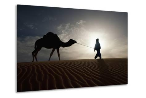 Silhouette of Berber Leading Camel across Sand Dunes at Dusk in the Erg Chebbi-Design Pics Inc-Metal Print