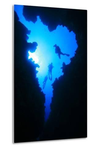 Scuba Divers Descend into Underwater Cavern, Silhouetted against Sun-Rich Carey-Metal Print