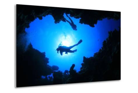 Scuba Divers Descend into an Underwater Cavern. Silhouettes against Sunburst-Rich Carey-Metal Print