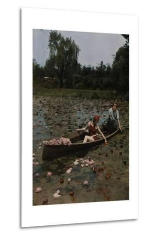 A Couple in a Boat Paddle on a Lily Pond and Collect Flowers-Charles Martin-Metal Print