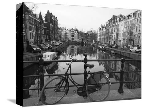 Black and White Imge of an Old Bicycle by the Singel Canal, Amsterdam, Netherlands, Europe-Amanda Hall-Stretched Canvas Print