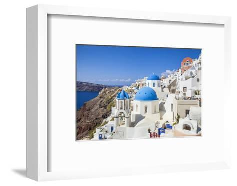 Greek Church with Three Blue Domes in the Village of Oia-Neale Clark-Framed Art Print