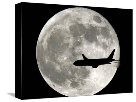 A Jet Plane Passes in Front of the Full Moon Above Surfside, Fla.--Stretched Canvas Print