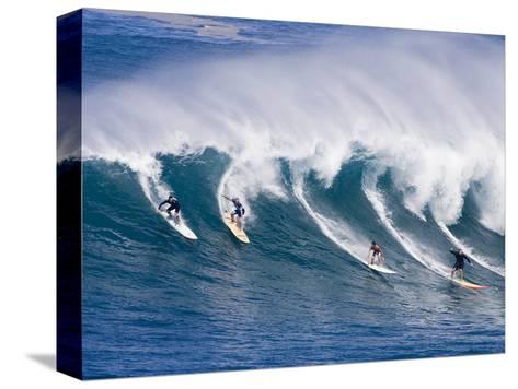 Surfers Ride a Wave at Waimea Beach on the North Shore of Oahu, Hawaii--Stretched Canvas Print