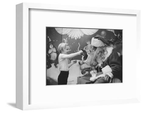Boy Kissing African American Santa Claus in Unidentified Department Store. 1970-Ralph Morse-Framed Art Print