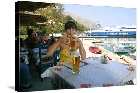 Woman Enjoying a Drink in a Harbourside Taverna, Poros, Kefalonia, Greece-Peter Thompson-Stretched Canvas Print