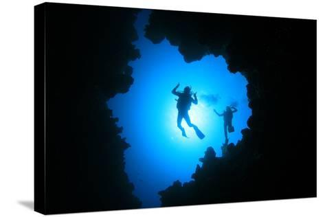 Couple of Scuba Divers Descend into an Underwater Cavern-Rich Carey-Stretched Canvas Print