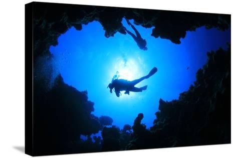 Scuba Divers Descend into an Underwater Cavern. Silhouettes against Sunburst-Rich Carey-Stretched Canvas Print
