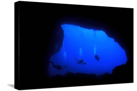 Into Darkness: Underwater Cave Scuba Diving Silhouettes-Rich Carey-Stretched Canvas Print