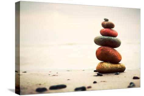 Stones Pyramid on Sand Symbolizing Zen, Harmony, Balance. Ocean in the Background-Michal Bednarek-Stretched Canvas Print