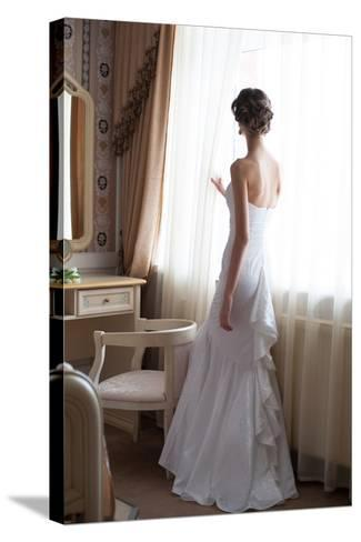 Beautiful Bride in White Wedding Dress Standing in Her Bedroom and Looking in Window- Malyugin-Stretched Canvas Print