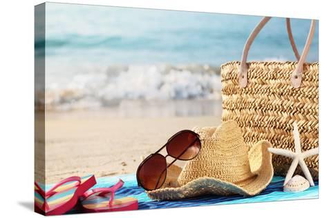 Summer Beach Bag with Straw Hat,Towel,Sunglasses and Flip Flops on Sandy Beach-Sofiaworld-Stretched Canvas Print