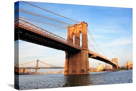 Brooklyn Bridge over East River Viewed from New York City Lower Manhattan Waterfront at Sunset.-Songquan Deng-Stretched Canvas Print
