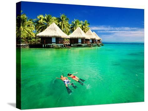 Couple Snorkling in Tropical Lagoon with over Water Bungalows-Martin Valigursky-Stretched Canvas Print