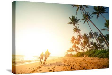 Couple Walking on the Sandy Beach with Palm Trees-Dudarev Mikhail-Stretched Canvas Print