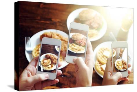Friends Using Smartphones to Take Photos of Food with Instagram Style Filter-evren_photos-Stretched Canvas Print