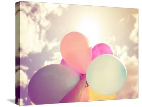 A Person Holding Multi Colored Balloons Done with a Retro Vintage Instagram Filter Effect-graphicphoto-Stretched Canvas Print