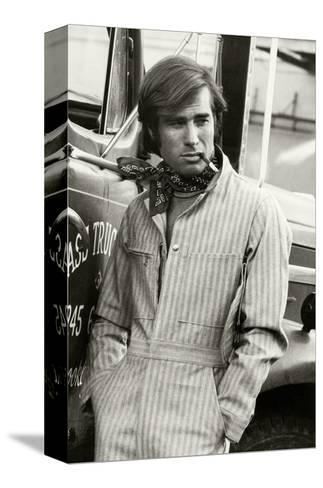 Man in Striped Denim Jumpsuit and Bandana Leaning Against a Truck with a Cigarette-Bruce Weber-Stretched Canvas Print