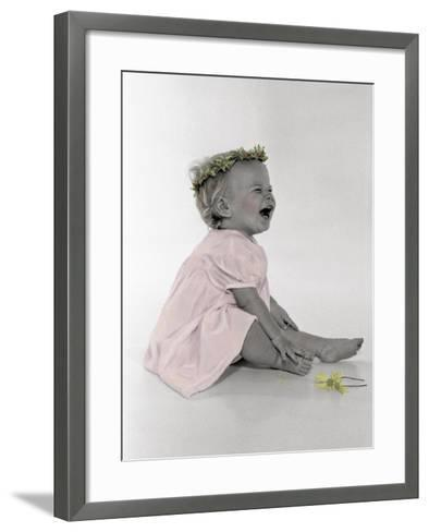Little Girl Sitting and Laughing with a Floral Ring on Head and Two Flowers in Front of Her-Nora Hernandez-Framed Art Print