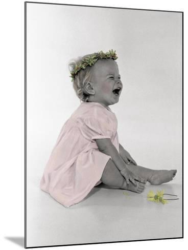 Little Girl Sitting and Laughing with a Floral Ring on Head and Two Flowers in Front of Her-Nora Hernandez-Mounted Giclee Print