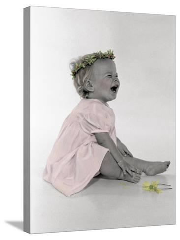 Little Girl Sitting and Laughing with a Floral Ring on Head and Two Flowers in Front of Her-Nora Hernandez-Stretched Canvas Print