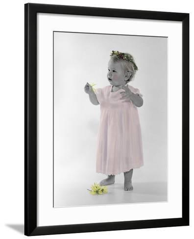 Little Girl Standing with Ring of Flowers on Head Holding Another Flower-Nora Hernandez-Framed Art Print