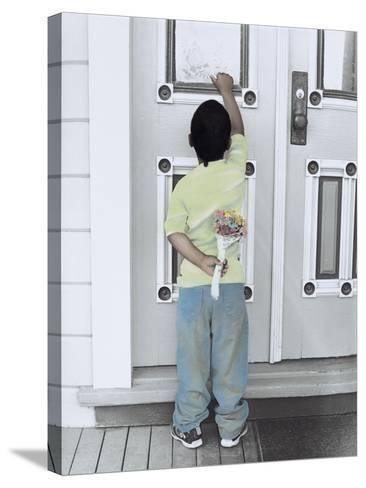 Boy Holding a Bouquet of Flowers Behind His Back While Knocking on the Door-Nora Hernandez-Stretched Canvas Print