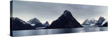 A Cone-Shaped Mountain Rises from the Dark Waters of an Arctic Fjord Beneath a Storm Laden Sky-Jason Edwards-Stretched Canvas Print