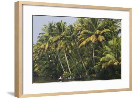 People Holding Red Umbrellas Ride in a Canoe Through the Backwaters-Kelley Miller-Framed Art Print