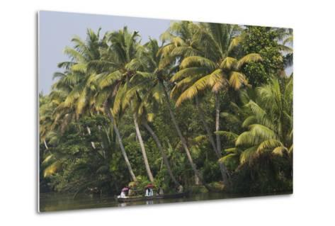 People Holding Red Umbrellas Ride in a Canoe Through the Backwaters-Kelley Miller-Metal Print