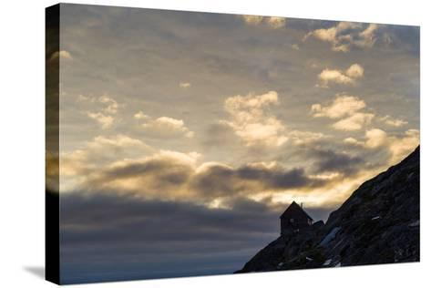 The Silhouette of a Cottage Perched on a Rocky Outcrop on an Arctic Island-Jason Edwards-Stretched Canvas Print