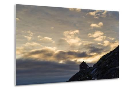 The Silhouette of a Cottage Perched on a Rocky Outcrop on an Arctic Island-Jason Edwards-Metal Print
