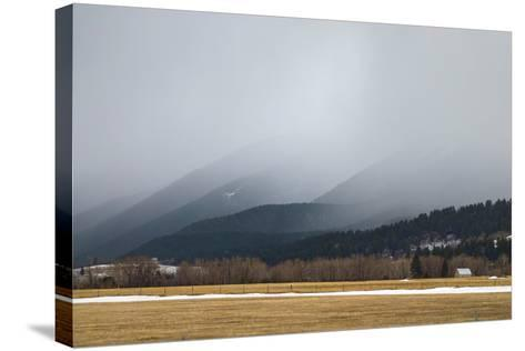 A Spring Storm Hovers over a Barn in Cottonwood Canyon of the Gallatin Range, Near Bozeman, Montana-Gordon Wiltsie-Stretched Canvas Print