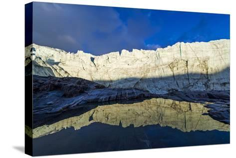 The Setting Sun Reflects the Sheer Ice Cliff of a Glacier Fracture Zone in a Pond-Jason Edwards-Stretched Canvas Print