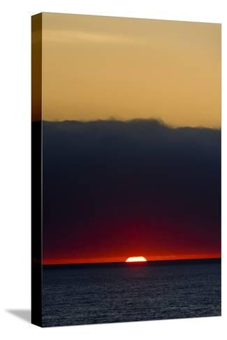 A Slither of Sunlight Pierces a Storm Cloud Above a Darkened Ocean at Sunset-Jason Edwards-Stretched Canvas Print