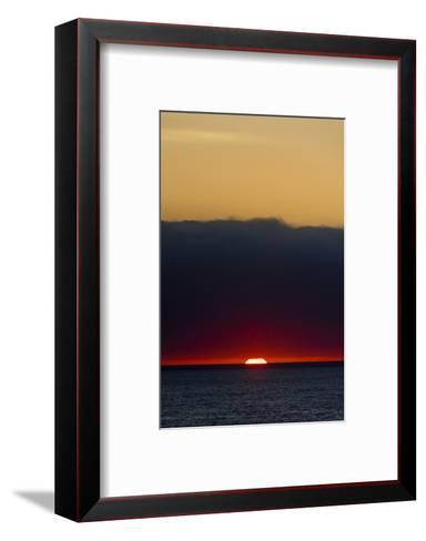 A Slither of Sunlight Pierces a Storm Cloud Above a Darkened Ocean at Sunset-Jason Edwards-Framed Art Print