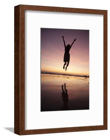 A Woman Jumping on the Beach at Sunset-Macduff Everton-Framed Art Print
