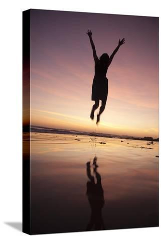 A Woman Jumping on the Beach at Sunset-Macduff Everton-Stretched Canvas Print