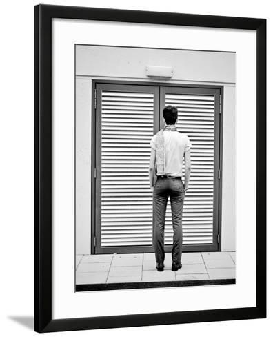 A Young Man Standing in the Street Looking at a Pair of Doors-India Hobson-Framed Art Print