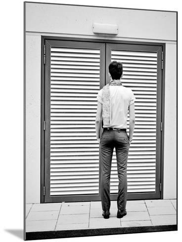 A Young Man Standing in the Street Looking at a Pair of Doors-India Hobson-Mounted Photographic Print