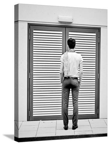 A Young Man Standing in the Street Looking at a Pair of Doors-India Hobson-Stretched Canvas Print