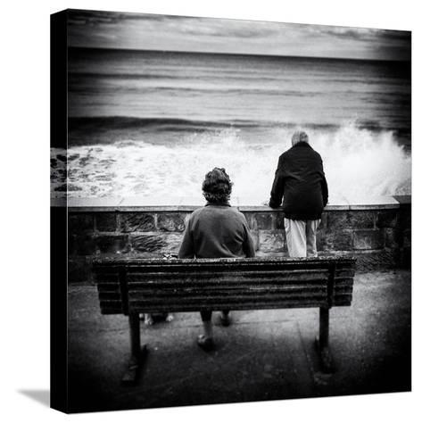 Elderly Couple Watch the Waves-Rory Garforth-Stretched Canvas Print