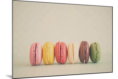 A Rainbow Selection of Sweet French Macarons Sitting in a Row.-Laura Evans-Mounted Photographic Print