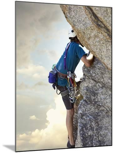 Young man rock climbing up a vertical cliff--Mounted Photographic Print