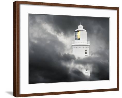 Lighthouse Emerging From Dark Clouds-Paul Hardy-Framed Art Print