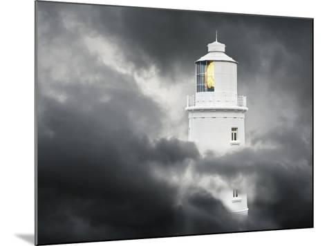 Lighthouse Emerging From Dark Clouds-Paul Hardy-Mounted Photographic Print