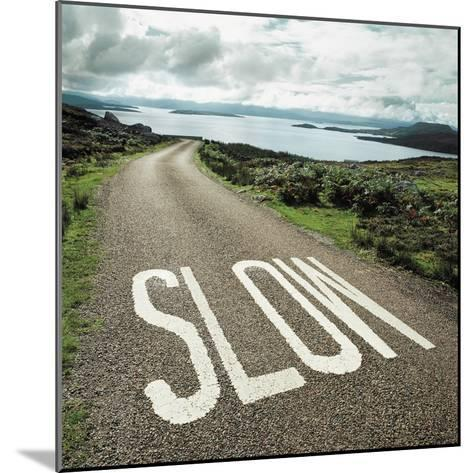 Road leading to the ocean with 'slow' painted on it--Mounted Photographic Print