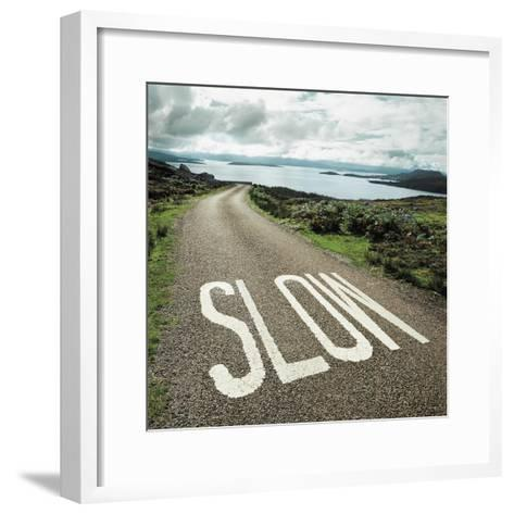 Road leading to the ocean with 'slow' painted on it--Framed Art Print