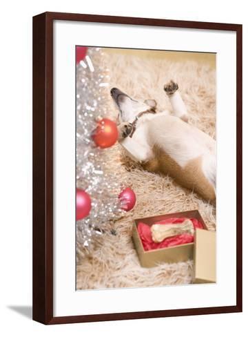 Dog Lying on Rug by Christmas Tree--Framed Art Print