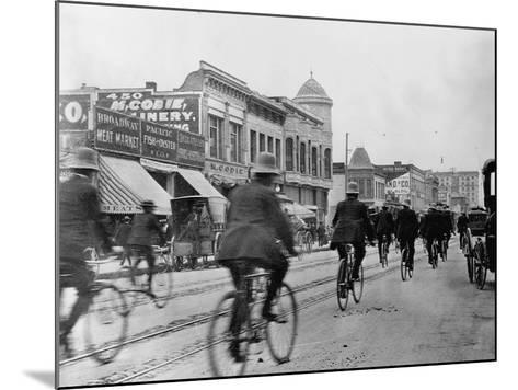 Los Angeles Police Officers Bicycling Past Broadway Storefronts--Mounted Photographic Print